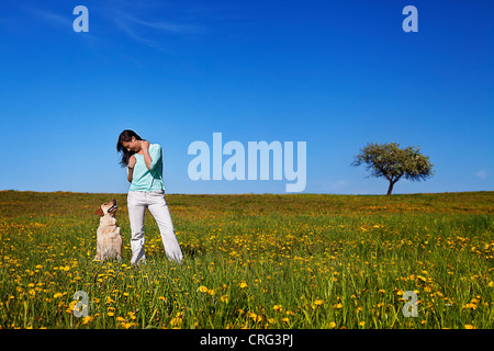 pretty girl with her dog on the meadow - Stock Photo