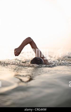 Teenage boy swimming in water - Stock Photo