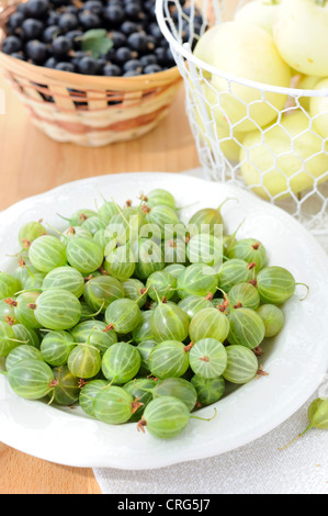 Gooseberries, currants and apples on a wooden table - Stock Photo