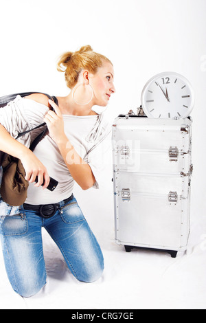 young blond woman under time pressure, looking at a clock - Stock Photo