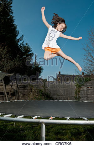 Smiling girl jumping on trampoline - Stock Photo