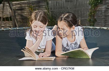 Girls reading books on trampoline - Stock Photo