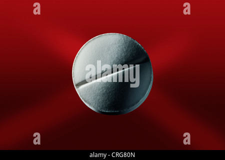 Close up of pill on red surface - Stock Photo
