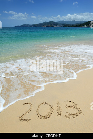 2013 written in the sand on Grand Anse Beach looking towards St George's, the capital of Grenada, West Indies. - Stock Photo