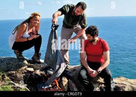 Spain, St. James Way: Pilgrims burning old walking cloths in Finisterre after the pilgrimage to Santiago de Compostela - Stock Photo