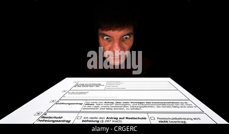 man looking at a sshedule for private insolvency - Stock Photo