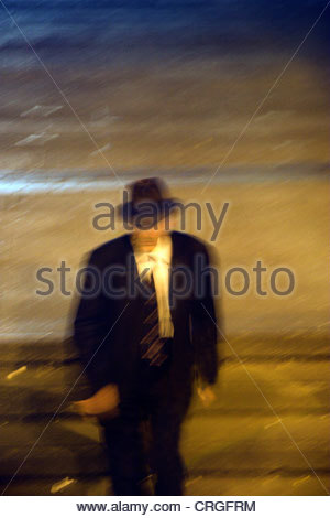 Mysterious man wearing a suit and trilby hat at night. London, UK. - Stock Photo