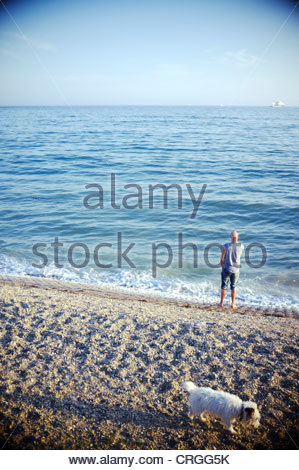 Lonely man and his dog, on a beach in Cornwall,UK. - Stock Photo
