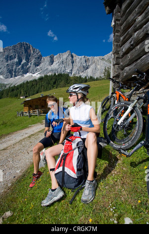 man and woman with mountain bikes sitting in front of an alpine cabin, having a break, Austria, Gmunden - Stock Photo