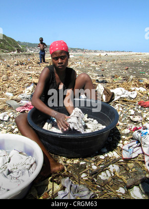 woman doing her laundry in a plastic bowl at a beach full of flotsam, small boy walking in the background, Haiti, - Stock Photo