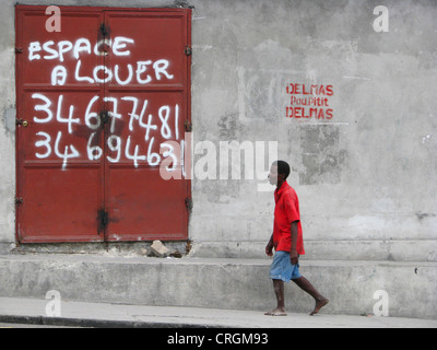 man walking along a concrete wall with an iron door offering space for rent, Haiti, Province de l'Ouest, Delmas, - Stock Photo