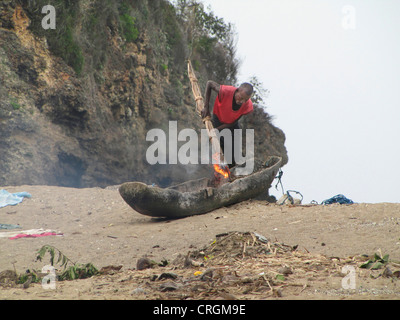 Man repairing his fisherboat made of a hollowed-out mango-tree, painting it with tar with a burning torch, Haiti, - Stock Photo