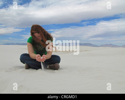 Young redheaded woman let white sand running throught her fingers, USA, New Mexico, White Sands National Monument, - Stock Photo