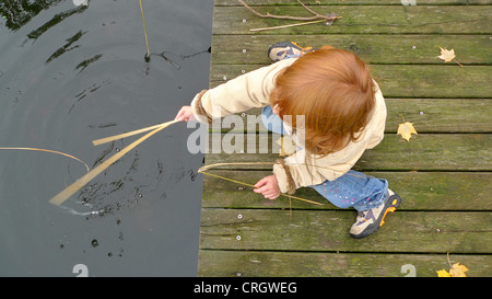 child sitting on a boardwalk dipping reed into the water - Stock Photo