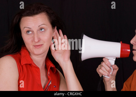 woman shouting into a megaphone to young woman - Stock Photo