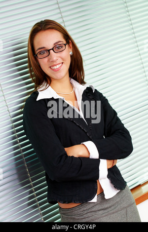 young businesswoman in an office smiling and wearing glasses, with folded arms - Stock Photo