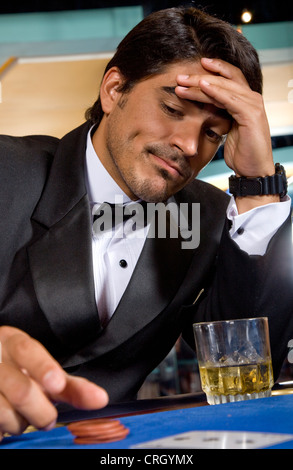 stressed poker player with his hand on his forehead, jetons and a whiskey glass - Stock Photo