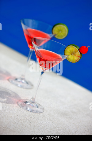 cocktails in martini glasses at a swimming pool - Stock Photo