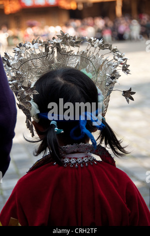 Miao girl from behind with a traditional silver crown, Xijiang Miao village, China - Stock Photo