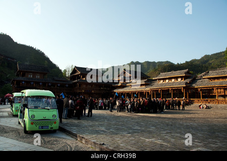 Green buses waiting for Chinese tourists after the Miao dancers show, Xijiang Miao village, China - Stock Photo