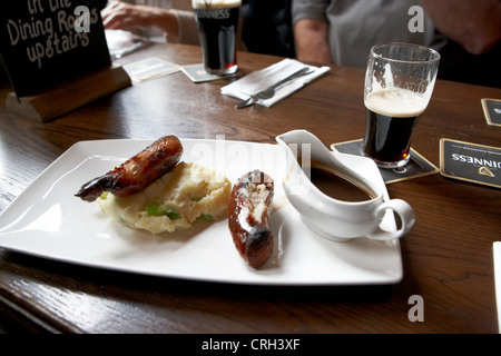 champ and sausages with guinness for lunch in a pub in ireland - Stock Photo