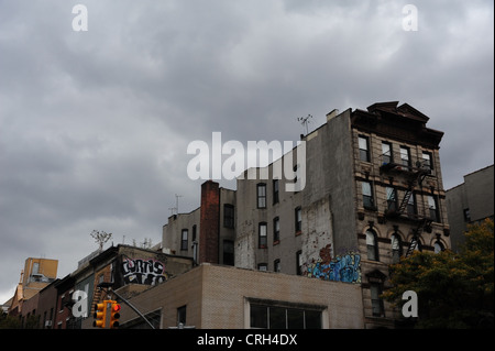 Grey sky view 5-storey brick tenements, graffiti cement render side walls, St Mark's Place at 2nd Avenue, East Village, - Stock Photo