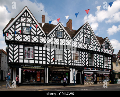 This medieval half timbered black and white building housing modern shops Warwick England survived the 1694 fire - Stock Photo