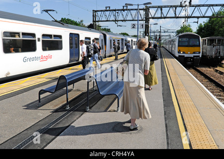 Women & other passengers waiting on train station platform to board choice of two Greater Anglia commuter trains - Stock Photo