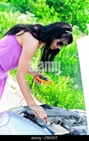 Woman controls lead–acid battery charge with voltmeter - Stock Photo