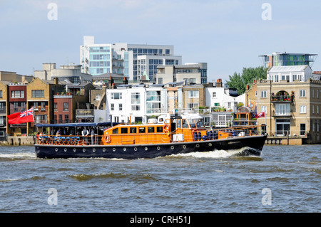 Motor launch Havengore on River Thames passing The Grapes riverside Inn at Limehouse assumed private hospitality - Stock Photo