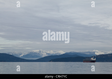 A cargo ship waits in the English Channel along Vancouver's coastline on an overcast winter day. - Stock Photo