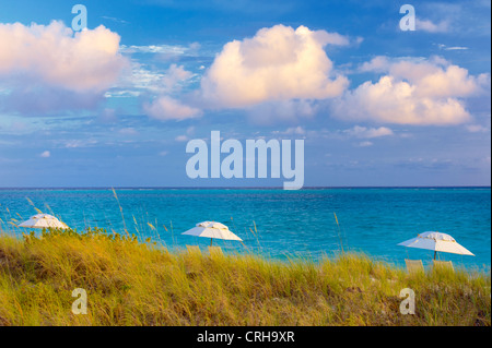 Three umbrellas and three clouds. Grace Bay, Providenciales. Turks and Caicos. - Stock Photo