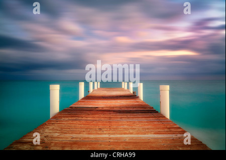 Pier at sunrise in Grace Bay. Providenciales. Turks and Caicos. - Stock Photo