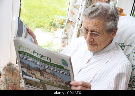 Elderly woman looking at properties on the property pages in a local paper - Stock Photo