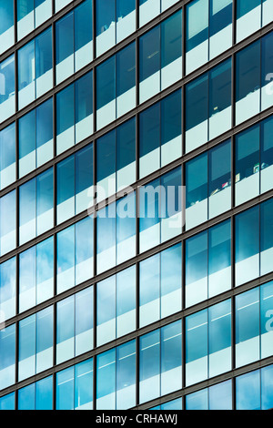 Stormy rain clouds reflected in Office block glass windows. Tottenham Court road London - Stock Photo