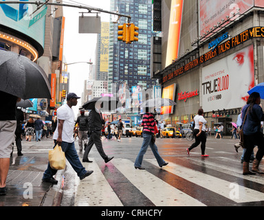 NEW YORK CITY, USA - JUNE 12: People crossing a street at rainy Times Square. June 12, 2012 in New York City, USA - Stock Photo