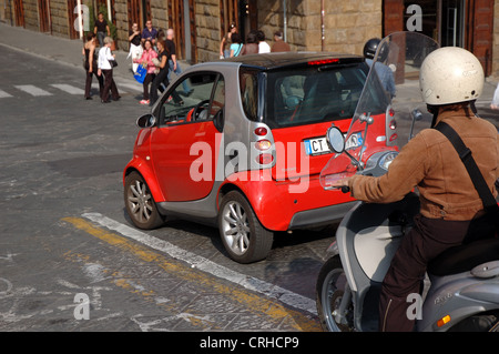 Bright red Smart Fortwo and a moped wait at a junction in Florence with tourists on a pedestrian crossing - Stock Photo