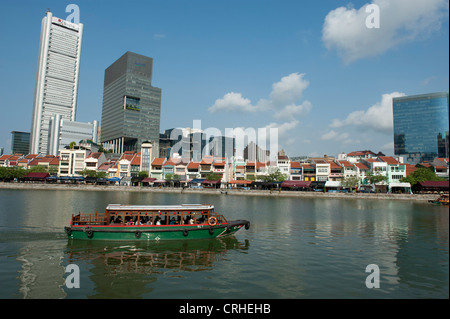 Excursion and ferry boat on Singapore River in front of Boat Quay at daytime in Singapore, Asia - Stock Photo