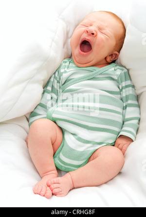 Yawning New Born Baby in the Bed - Stock Photo