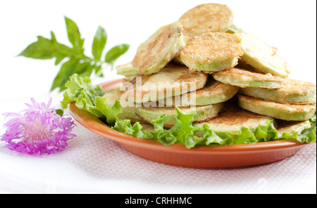 Fried zucchini on a brown dish. Courgettes fried in egg batter. - Stock Photo
