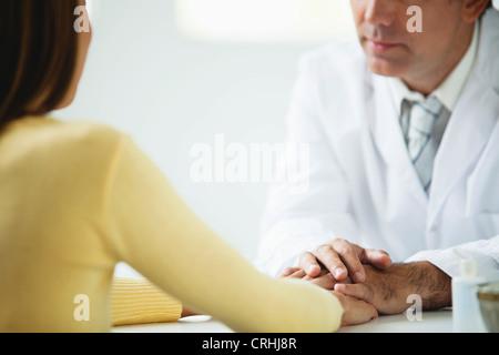 Doctor comforting patient - Stock Photo