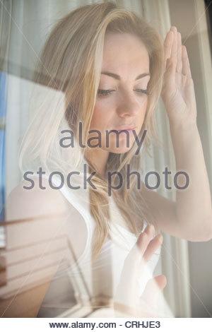 Woman gazing out window - Stock Photo