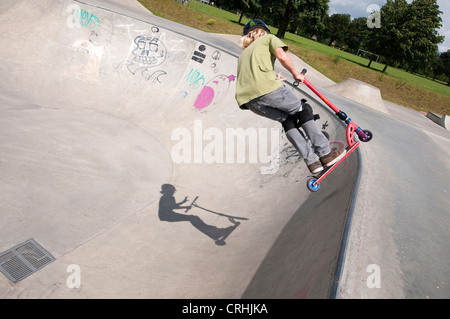 scooter rider in urban skate park bowl, eaton park, norwich, norfolk, england - Stock Photo