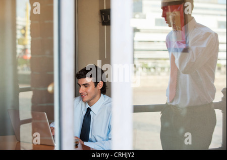 Businessman in office seen from outside of window, reflection of man using cell phone outdoors - Stock Photo