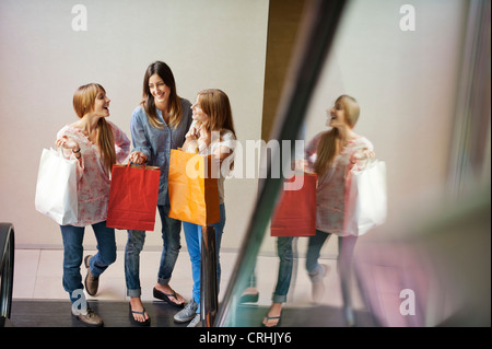 Young women carrying shopping bags, standing at bottom of escalator - Stock Photo