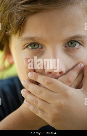 Boy covering mouth with hands - Stock Photo