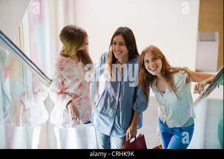 Young women standing on escalator, carrying shopping bags - Stock Photo