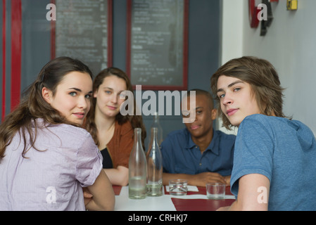 Young adult friends hanging out in cafe - Stock Photo