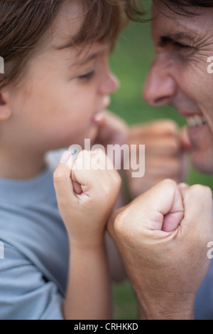 Father and son goofing off with fists clenched - Stock Photo