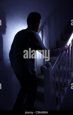 Young man walking upstairs late at night. - Stock Photo